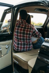 couple, man and woman are sitting in the car, the guy is hugging the girl. cinema. check shirt and white blouse, darkies