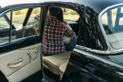 couple, man and woman are sitting in the car, the guy is hugging the girl. traveling together. check shirt and white blouse, darkies