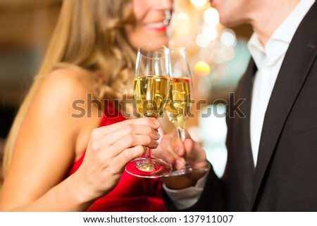 Couple, man and woman, drinking champagne in a fine dining restaurant, each with glass of sparkling wine in hand #137911007