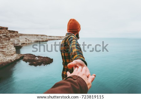 Couple Man and Woman holding hands follow enjoying cold sea landscape on background Love and Travel emotions Lifestyle concept. Young family traveling active adventure vacations.  #723819115