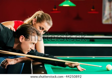 Couple (man and woman) in a billiard hall playing Pool