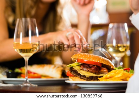 Couple - Man And Woman - In A Fine Dining Restaurant They Eat Fast Food, Burger And Fries, Closeup