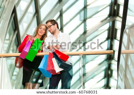 Couple - man and woman - in a shopping mall with colorful bags looking at their bought stuff