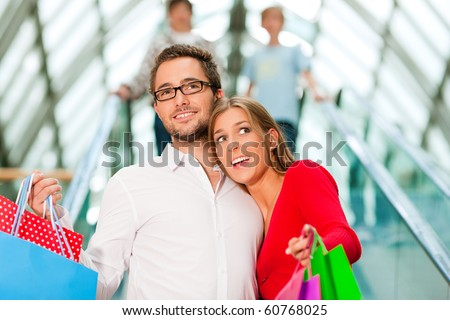 Couple - man and woman - in a shopping mall with colorful bags on an escalator
