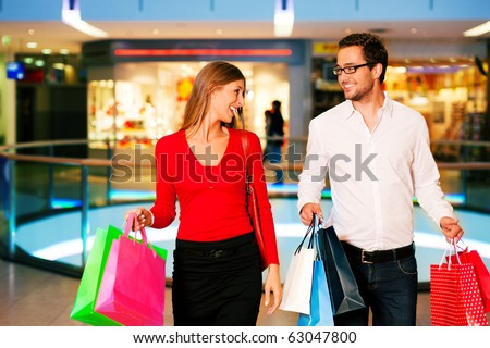 Couple - man and woman - in a shopping mall with colorful bags simply having fun