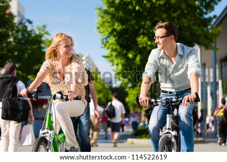 Couple - man and woman - riding their bikes or bicycles in their free time and having fun on a sunny summer day