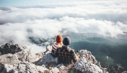 Couple Man and Woman sitting on cliff enjoying mountains and clouds landscape Love and Travel happy emotions Lifestyle concept. Young family traveling active adventure vacations