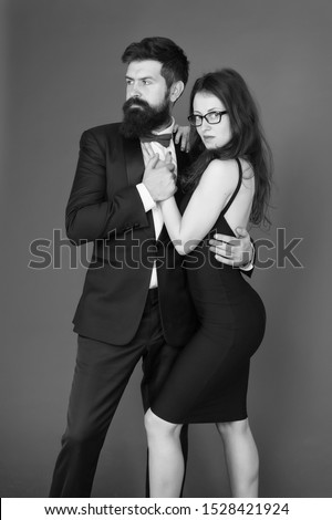 Couple man in tuxedo and elegant girl. Man bearded hipster and woman in formal dress red background. Formal fashion and elegant clothes. Luxury fashion boutique. Fashion clothes shop. Official event. #1528421924