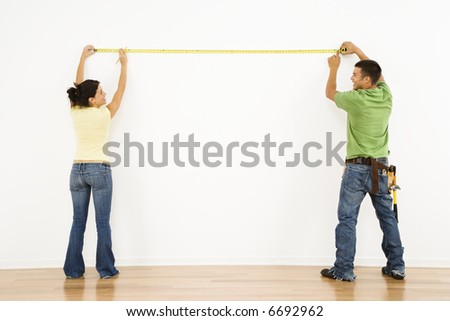 Couple measuring interior wall and smiling.