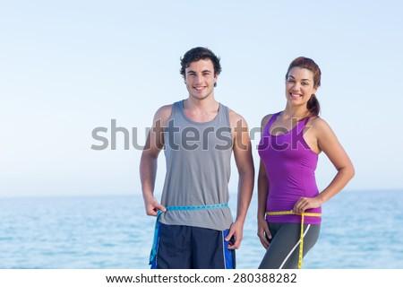 Couple measuring their waist at the beach