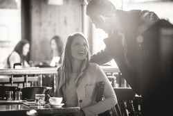 Couple meeting at the bar smiling at each other