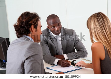 Couple meeting businessman in office