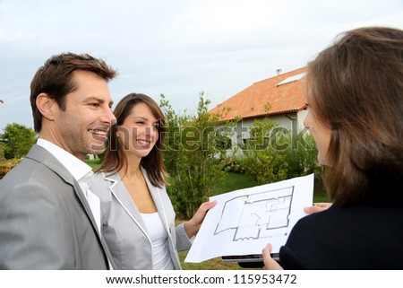 Couple meeting saleswoman on construction site