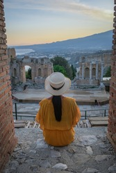 couple men and woman visit Ruins of Ancient Greek theatre in Taormina on background of Etna Volcano, Italy. Taormina located in Metropolitan City of Messina, on east coast of island of Sicily Italy