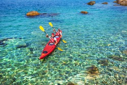 Couple men floating on a sea kayaking. Traveling by kayak outdoors on a summer day.