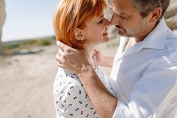 couple middle-age years in white shirts walks between sandstone rocks. holding hands, hugging, kissing. happiness love. standing against the sky. close-up portraits gentle
