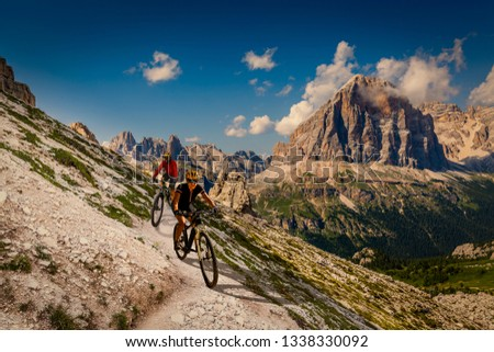 Couple mountain bike rider on electric bike, e-mountainbike rides up mountain trail. Woman and Man riding on e-bike in Dolomites mountains landscape. Cycling trail track. Outdoor sport activity. #1338330092