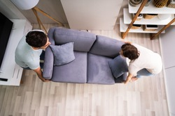 Couple Moving And Carrying Sofa Furniture Or Couch
