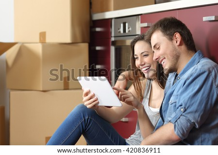 Couple moving home and buying on line with a tablet sitting on the floor in the kitchen