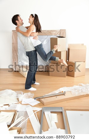 Couple moving in happy and excited in new home. Young interracial couple with moving boxes and furniture assembly in new house or apartment. Caucasian man and Asian woman embracing.