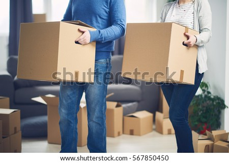 Couple moving into new apartment. Lot of packing cartons around them. #567850450