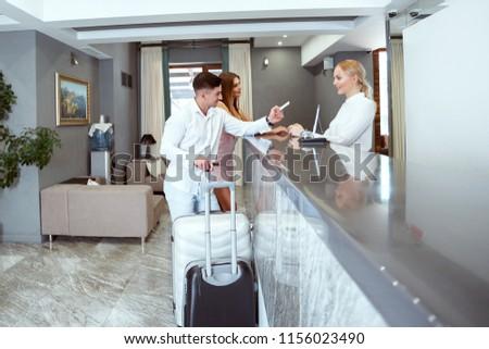 couple near reception desk in hotel #1156023490