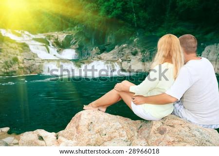 Couple near waterfall on sunrise time