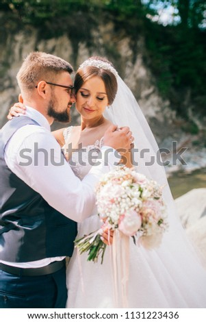Couple newlyweds bride and groom kiss laughs and smiles to each other, happy and joyful moment. Man and woman in wedding clothes sit on the rock background mountain river. Wedding tender moments. #1131223436