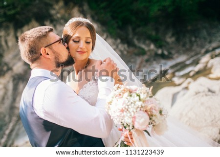 Couple newlyweds bride and groom kiss laughs and smiles to each other, happy and joyful moment. Man and woman in wedding clothes sit on the rock background mountain river. Wedding tender moments. #1131223439