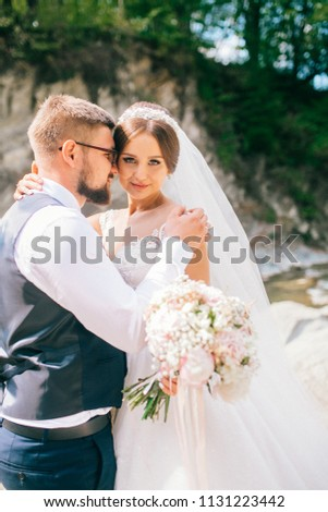 Couple newlyweds bride and groom kiss laughs and smiles to each other, happy and joyful moment. Man and woman in wedding clothes sit on the rock background mountain river. Wedding tender moments. #1131223442