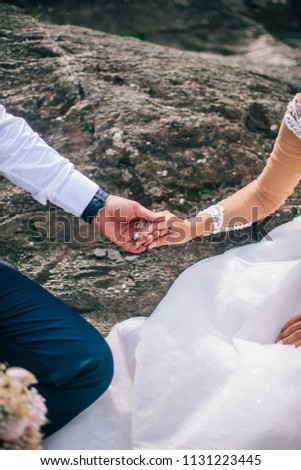 Couple newlyweds bride and groom kiss laughs and smiles to each other, happy and joyful moment. Man and woman in wedding clothes sit on the rock background mountain river. Wedding tender moments. #1131223445