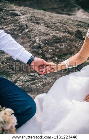 Couple newlyweds bride and groom kiss laughs and smiles to each other, happy and joyful moment. Man and woman in wedding clothes sit on the rock background mountain river. Wedding tender moments. #1131223448