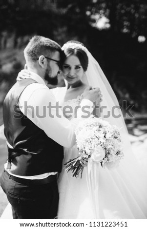 Couple newlyweds bride and groom kiss laughs and smiles to each other, happy and joyful moment. Man and woman in wedding clothes sit on the rock background mountain river. Wedding tender moments. #1131223451