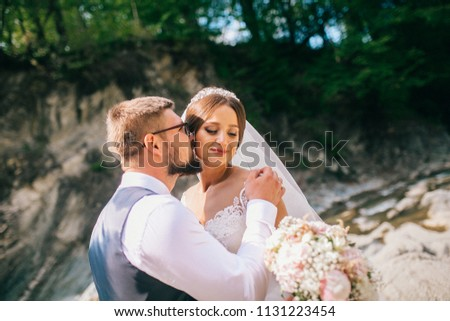 Couple newlyweds bride and groom kiss laughs and smiles to each other, happy and joyful moment. Man and woman in wedding clothes sit on the rock background mountain river. Wedding tender moments. #1131223454
