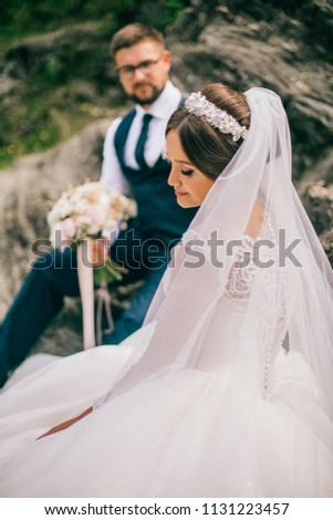 Couple newlyweds bride and groom kiss laughs and smiles to each other, happy and joyful moment. Man and woman in wedding clothes sit on the rock background mountain river. Wedding tender moments. #1131223457