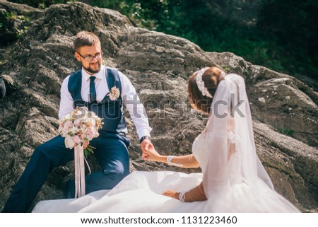 Couple newlyweds bride and groom kiss laughs and smiles to each other, happy and joyful moment. Man and woman in wedding clothes sit on the rock background mountain river. Wedding tender moments. #1131223460