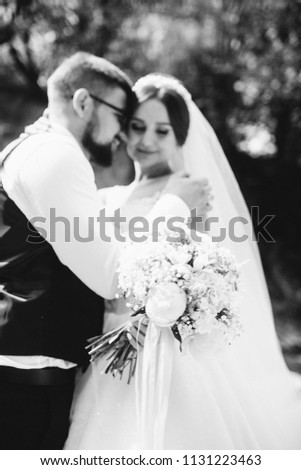 Couple newlyweds bride and groom kiss laughs and smiles to each other, happy and joyful moment. Man and woman in wedding clothes sit on the rock background mountain river. Wedding tender moments. #1131223463