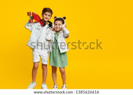 Couple of adorable stylish children with skateboard smiling and listening to music in headphones while standing against bright yellow background. Brother and sister hugging #1385626616