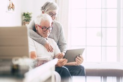 couple of adult seniors smiling and looking at the tablet - retired people using technology at home - woman hug the man with love - forever together nice old people enjoy technology