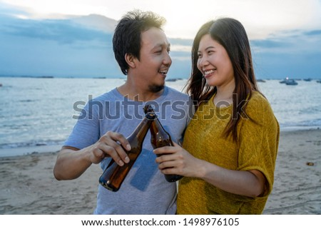 Couple of asian cheerful friends have party drinks with cheer beer bottles at the beach when sunset time, celebration and relax when vacation with lover concept #1498976105