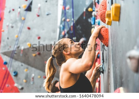 couple of athletes climber moving up on steep rock, climbing on artificial wall indoors. Extreme sports and bouldering concept ストックフォト ©