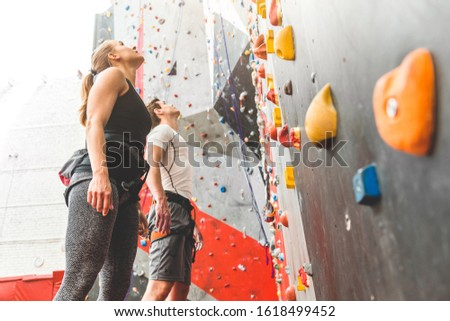 couple of athletes climber stand and watch on steep rock, climbing on artificial wall indoors. Extreme sports and bouldering concept.