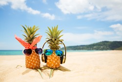 Couple of attractive pineapples in love on the sand against turquoise sea. Wearing stylish mirrored sunglasses. Tropical summer vacation concept. Sunny day on the beach of tropical island. Honeymoon