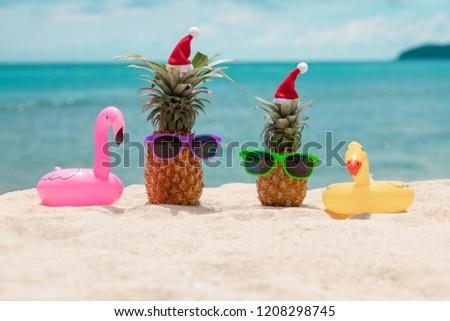 299bb61f Couple of attractive pineapples in stylish mirrored sunglasses on sand  against turquoise sea and beach umbrella