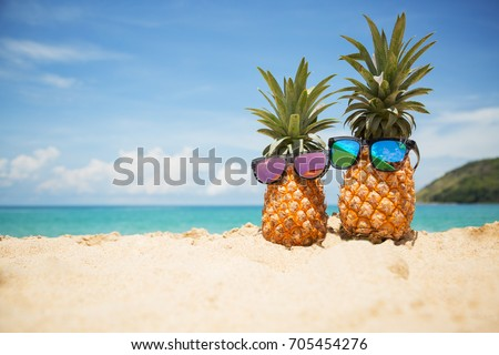 Couple of attractive pineapples in stylish mirrored sunglasses on the sand against turquoise sea. Tropical summer vacation concept. Sunny day on the beach of tropical island. Honeymoon. Family holiday