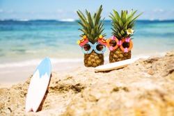 Couple of attractive pineapples surfers in stylish sunglasses on the rocks against turquoise sea. Having stylish surfboards. Tropical summer vacation concept. Sunny day on the beach. Family holiday