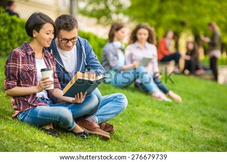 Couple of attractive smiling students dressed casual  studying outdoors on campus at the university.