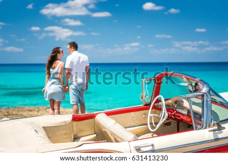 Couple of beautiful brunette curly woman and handsome man are standing on the coastline of caribbean sea near red retro convertible car cabriolet at summer sunny day