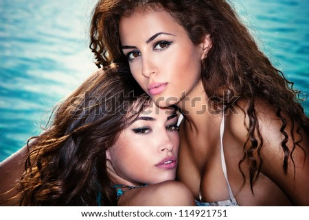 couple of beautiful girls portrait by the swimmingpool