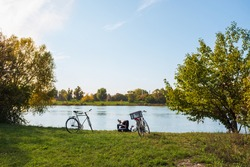 Couple of Bicyclists resting on a river bank in autumn on a sunny day. Sunlight, colorful foliage, clean River.